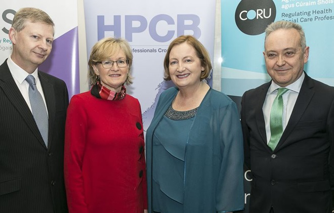 Four people standing in front of an HPCB conference poster